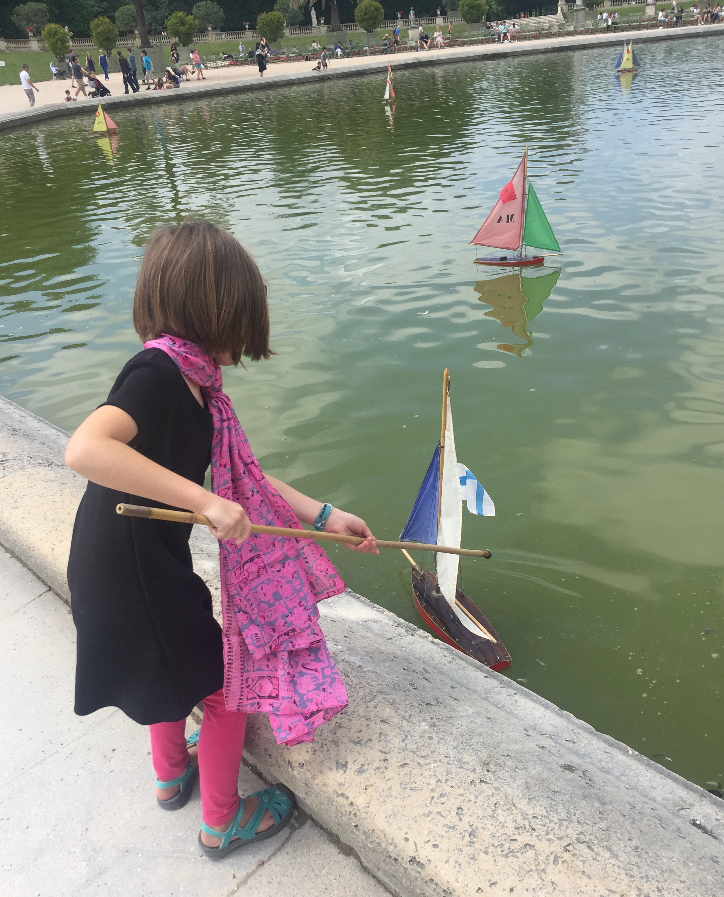 Young girl pushing a sailboat with a stick in Paris. When you research your destination, you can find things to do with your kids.