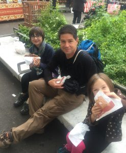 Research your destination to find the best foods, like these crepes.  Dad and two girls eating crepes in Paris.